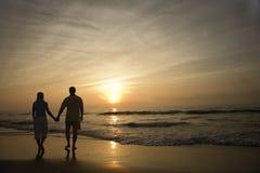 Paare, die auf Strand am Sonnenuntergang gehen Lizenzfreies Stockfoto