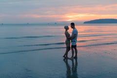 Paare, die auf Strand am Sonnenuntergang, am jungen touristischen Mann und an der Frauen-Umarmung auf Küste umfassen lizenzfreies stockbild