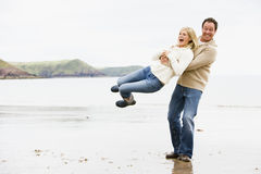 Paare, die auf Strand spielen lizenzfreie stockfotografie