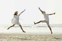 Paare, die auf Strand springen Lizenzfreies Stockbild