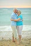 Paare, die auf Strand umarmen Lizenzfreie Stockfotografie