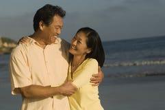 Paare, die auf Strand umfassen Stockbild