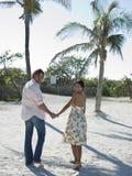 Paare, die auf Strand umfassen Stockfotos