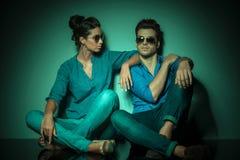 Paare, die auf Studiohintergrund sitzen Lizenzfreie Stockbilder