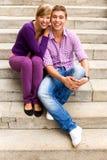 Paare, die auf Treppen sitzen Stockfoto