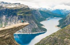 Paare, die auf Trolltunga Norwegen aufwerfen stockfotografie