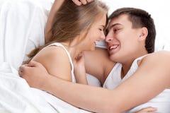 Paare, die auf weißem Bett liegen Stockfotografie