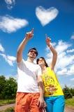 Paare, die auf Wolkeninneres zeigen Lizenzfreies Stockfoto