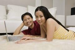 Paare, die auf Wolldecke mit Laptop liegen Lizenzfreies Stockbild
