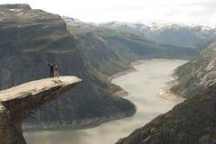 Paare, die auf Zunge der Schleppangel, Norwegen springen Lizenzfreies Stockbild
