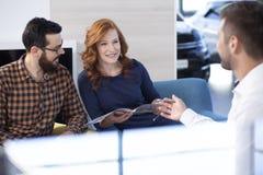 Paare, die Autoangebot betrachten und mit einem Händler in einem Auto sho sprechen stockbild