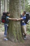 Paare, die Baum im Wald umarmen stockfoto