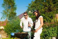 Paare, die BBQ im Garten am Sommer tun Lizenzfreies Stockbild