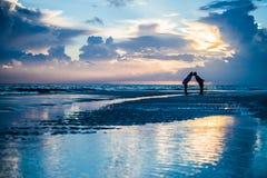 Paare, die bei Sonnenaufgang auf einem Strand küssen lizenzfreies stockbild