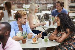 Paare, die bei Tisch im Kneipen-Garten zusammen genießt Getränk sitzen lizenzfreie stockbilder
