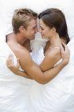 Paare, die beim Bettlächeln liegen Lizenzfreie Stockfotografie