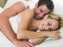 Paare, die beim Bettlachen liegen lizenzfreie stockfotos