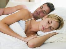 Paare, die beim Bettschlafen liegen Lizenzfreies Stockfoto