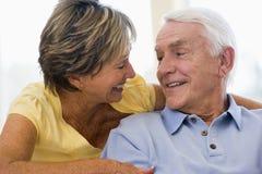 Paare, die beim Wohnzimmerlächeln sich entspannen Stockfotos