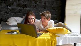 Paare, die in Bett-Gebrauchs-Laptop-Computer glücklichem Lächeln plaudert on-line--, junges Mädchen und Mann am Schlafzimmer-Morg stock video footage