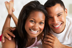 Paare, die in Bett-tragenden Pyjamas sich entspannen Lizenzfreie Stockbilder