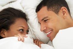 Paare, die in Bett-tragenden Pyjamas sich entspannen Stockfotografie