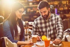 Paare, die Blaupausen im Café betrachten stockfotos