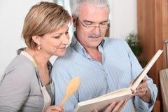 Paare, die Buch betrachten lizenzfreie stockfotos