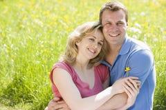 Paare, die das Blumensitzen lächeln draußen, anhalten lizenzfreie stockfotografie