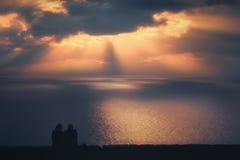 Paare, die das Meer bei Sonnenuntergang aufpassen Stockfoto