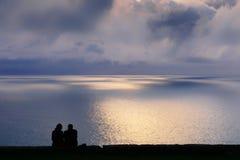 Paare, die das Meer bei Sonnenuntergang aufpassen Stockbilder