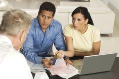 Paare, die dem Berater Dokumente und Kreditkarten geben Lizenzfreie Stockfotografie