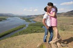 Paare, die in den Bergen küssen Lizenzfreie Stockfotos