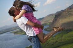 Paare, die in den Bergen küssen Stockfotos