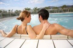 Paare, die in den Heißwassern sich entspannen Stockfotos