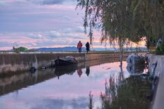 Paare, die in den Herbstsonnenuntergang geht durch einen Kanal mit Booten gehen stockbild