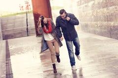Paare, die in den Regen laufen Stockfotos