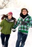 Paare, die in den Schnee laufen Stockfotos