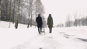 Paare, die in den Schnee, Schlitten ziehend gehen Langsames MO stock video footage