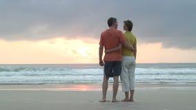 Paare, die den Sonnenaufgang auf einem Strand erwägen stock video