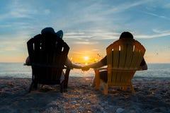 Paare, die den Sonnenuntergang auf Strand aufpassen Lizenzfreie Stockfotografie