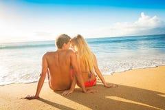 Paare, die den Sonnenuntergang auf tropischen Strand-Ferien aufpassen stockbild