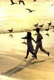 Paare, die in den Strand laufen lizenzfreie stockfotografie