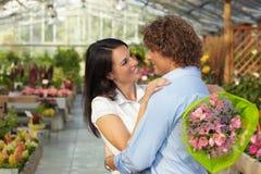 Paare, die in der Blumenbaumschule umarmen Lizenzfreie Stockfotos