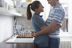 Paare, die in der Küche umfassen Lizenzfreie Stockbilder