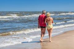 Paare, die an der Küstenlinie schlendern Stockbild