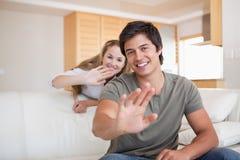 Paare, die an der Kamera wellenartig bewegen Lizenzfreies Stockfoto