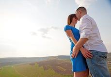 Paare, die in der Landschaft umarmen lizenzfreie stockbilder