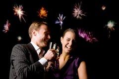 Paare, die an der Partei mit Feuerwerken im Hintergrund rösten Stockbild