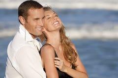 Paare, die in der romantischen Umarmung auf Strand lachen Lizenzfreies Stockfoto